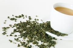 Hojas de té verdes y taza blanca Fotos de archivo