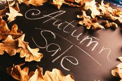 Hojas del amarillo y el otoño de la inscripción en una pizarra Fotos de archivo libres de regalías