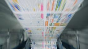 Hojas del periódico que mueven encendido un transportador rodante en la instalación tipográfica almacen de video