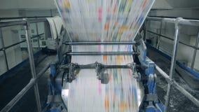 Hojas del periódico que ruedan en un transportador 4K metrajes