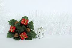 Hojas del verde y regalos rojos en un fondo blanco con una guirnalda blanca para los días de fiesta Imagenes de archivo