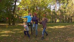 Hojas felices del amarillo de los tiros de los muchachos en otoño almacen de video
