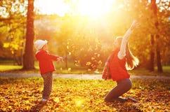 Hojas felices el jugar y del tiro de la muchacha de la madre y del niño de la familia en a Fotografía de archivo