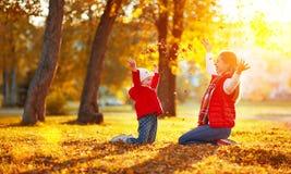 Hojas felices el jugar y del tiro de la muchacha de la madre y del niño de la familia en a Imágenes de archivo libres de regalías