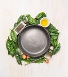 Hojas frescas de la espinaca con cocinar los ingredientes: aceite, nuez moscada moscada, ajo y olnion alrededor de una placa gris Imágenes de archivo libres de regalías