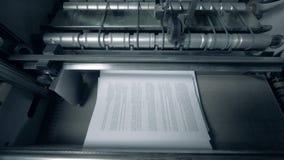 Hojas impresas con el texto en un transportador, visión superior metrajes