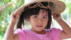 Hojas puestas muchacha asiática linda del sombrero en la cabeza metrajes