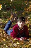Hojas que caen sobre muchacho sonriente feliz Imagen de archivo
