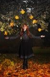 Hojas que hacen juegos malabares de la muchacha en parque del otoño Imagen de archivo libre de regalías