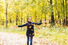 Hojas que lanzan de la muchacha adolescente atractiva en el aire Imagen de archivo libre de regalías