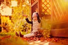 Hojas que lanzan de la muchacha feliz del niño en el paseo en jardín soleado del otoño Imagen de archivo libre de regalías