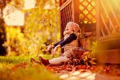 Hojas que lanzan de la muchacha feliz del niño en el paseo en jardín soleado del otoño Fotografía de archivo