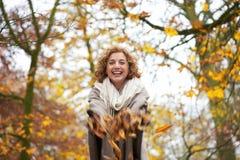 Hojas que lanzan de la mujer feliz Foto de archivo libre de regalías