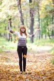 Hojas que lanzan del adolescente del Redhead en el bosque Imágenes de archivo libres de regalías