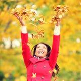 Hojas que lanzan felices de la mujer del otoño/de la caída Foto de archivo libre de regalías