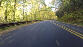 Hojas que soplan detrás del coche en Ridge Parkway azul