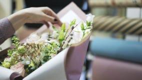 Hojas que sujetan con grapa del florista del papel de embalaje y ajuste de una cinta almacen de metraje de vídeo