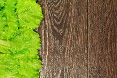 Hojas verdes de la ensalada de la lechuga en de madera Imagen de archivo