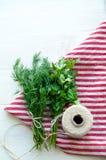 Hojas verdes del perejil y del eneldo en servilleta de lino natural en fondo de madera Foto de archivo
