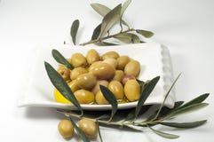 Hojas verdes olivas, aceitunas en una placa blanca Imagenes de archivo