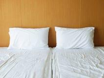 Hojas y almohadas blancas desordenadas del lecho Fotos de archivo