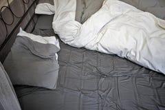 Hojas y almohadas de una cama sin hacer Imagenes de archivo