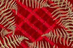 Hojas y helecho tropicales brillantes de oro de la rama en fondo del color rojo en estilo mínimo foto de archivo libre de regalías
