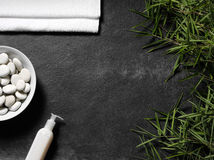 Hojas y toalla del bambú con crema en un fondo de la pizarra Imagen de archivo