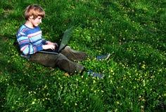 Hojeador (el niño con el cuaderno sienta la hierba verde) Imagen de archivo libre de regalías