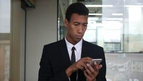 Hojeando en Smartphone, hombre de negocios negro en oficina almacen de metraje de vídeo