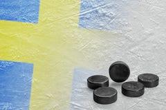 Hokejowi krążki hokojowi i wizerunek szwedzi zaznaczają na lodzie Obrazy Stock