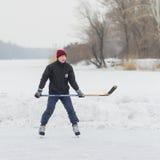 年轻hokey球员Outdor画象用在一条冻河德聂伯级的棍子 免版税库存图片