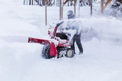Man using snow removal machine. Hokkaido, Japan - 28 December 2017 - Unidentified man use his red snow removal machine to clear path way at a park in Hokkaido royalty free stock images