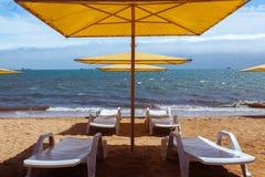 Holów krzesła i kolorowi parasole przy plażą przy słonecznym dniem obrazy royalty free