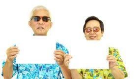 拿着白色空白的标志的愉快的亚洲资深夫妇准备好hol 免版税库存照片