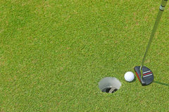 高尔夫球的一家平的顶头轻击棒俱乐部能滚动在杯子hol里面 图库摄影