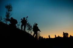 军事战士剪影有武器的在晚上 射击, hol 免版税库存照片