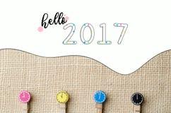 Hola 2017 con las pinzas de madera coloridas en fondo del saco de la arpillera Foto de archivo libre de regalías