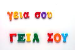 Hola en griego con alfabeto del juguete Imágenes de archivo libres de regalías