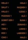 Hola en muchas idiomas, en color anaranjado Fotografía de archivo