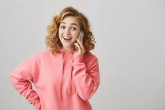 Hola es yo Retrato de hablar femenino rubio cabelludo rizado apuesto feliz en smartphone, sorprendido para recibir Fotografía de archivo