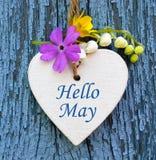 Hola la tarjeta de felicitación de mayo con el corazón y la primavera blancos decorativos florece en viejo fondo de madera azul Imagen de archivo libre de regalías