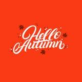 Hola letras escritas mano del otoño con las hojas del amarillo que caen y de la naranja Foto de archivo libre de regalías