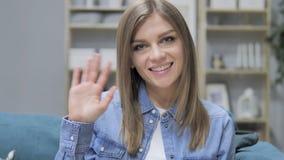 Hola, mano que agita de la chica joven a dar la bienvenida metrajes
