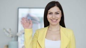 Hola, mano que agita de la mujer joven a la recepción almacen de video