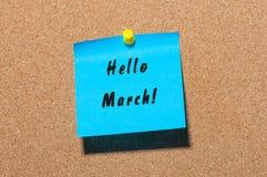 Hola marzo - escritura en un papel azul fijado en el noticeboard del corcho Principio del concepto de la primavera Foto de archivo libre de regalías