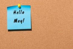 Hola mayo - texto en la etiqueta engomada azul fijada en el tablón de anuncios Concepto del resorte Imagenes de archivo
