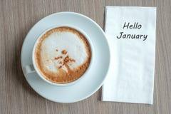 Hola palabra de enero con la taza de café caliente del capuchino en fondo de la tabla en la mañana Nuevo comienzo del Año Nuevo,  imagenes de archivo