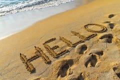 Hola saludo escrito en una playa arenosa de oro Fotografía de archivo