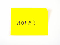 Hola! skriftligt på en klibbig anmärkning Arkivbild